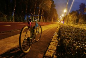 Classic parked bicycle near the road at night